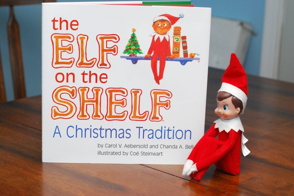 a Elf on the Shelf and an elf on the shelf book sitting on a table