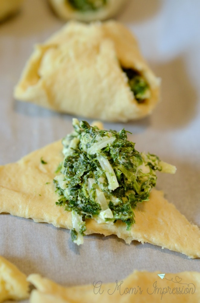 Put the cheesy spinach filling into the crescent rolls.