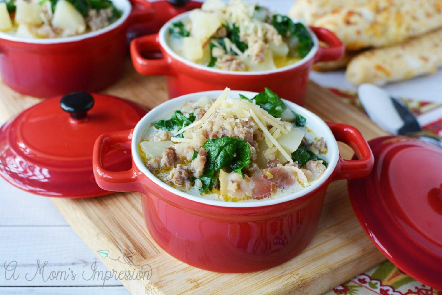 a bowl of pressure cooker zuppa toscana soup in a red crock on top of a cutting board