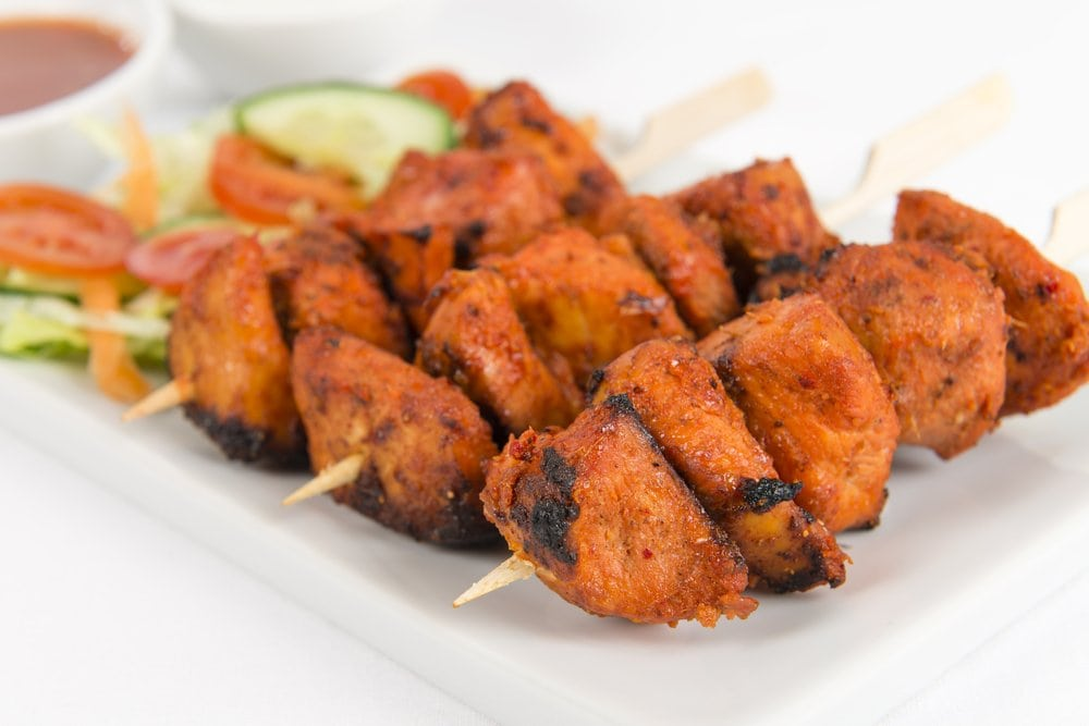 Pressure Cooker chicken skewers on a white plate with vegetables