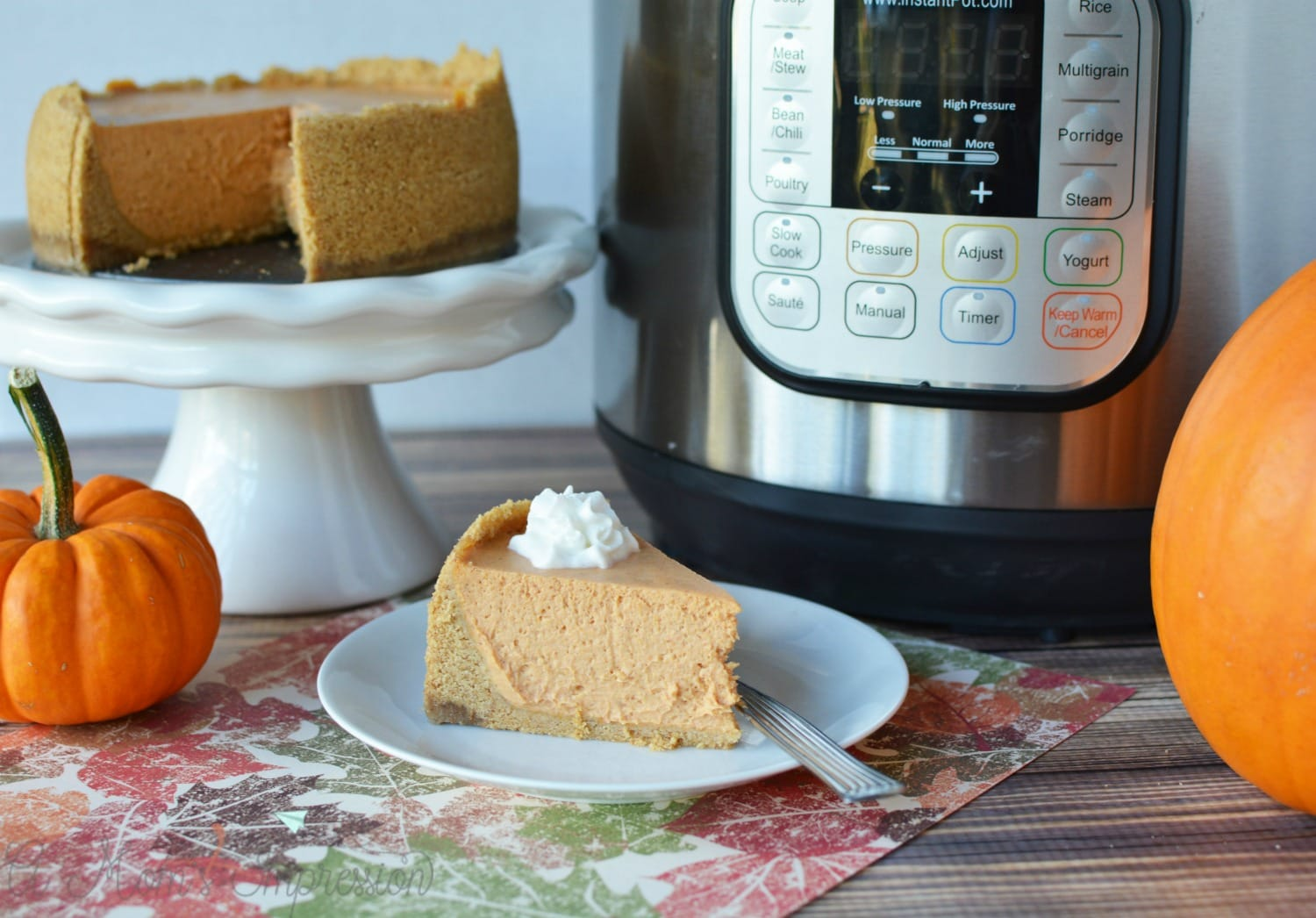 Instant Pot Pumpkin cheesecake sitting on a white plate with pumpkins.