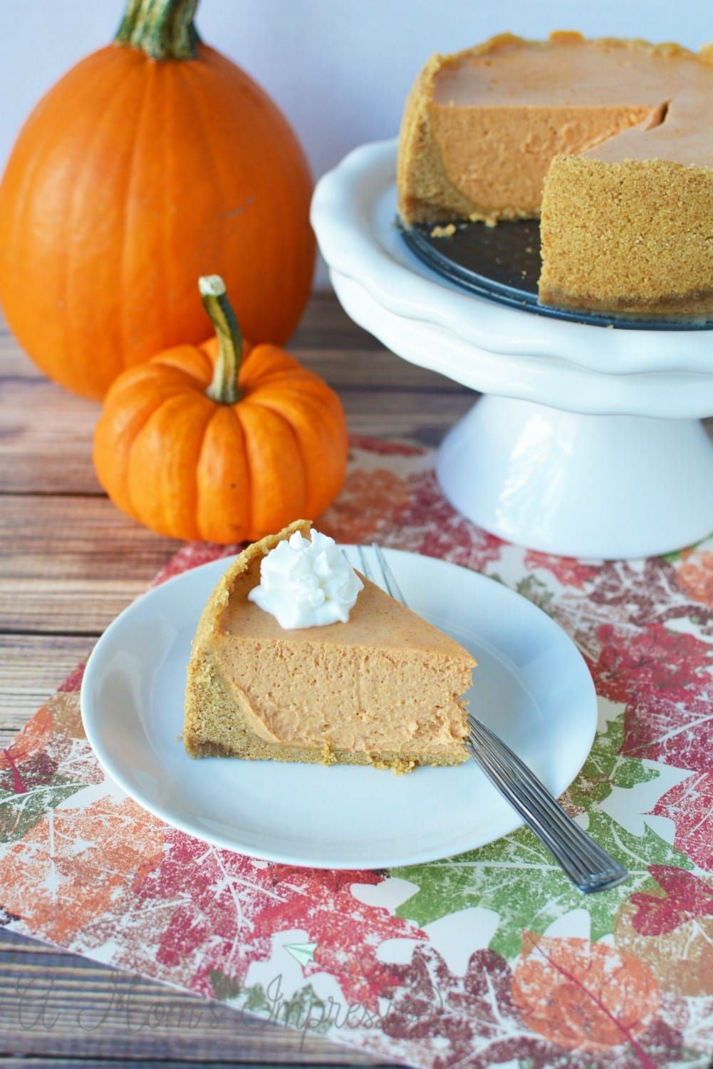 Instant Pot Pumpkin Cheesecake Recipe sitting on a table with two pumpkins.