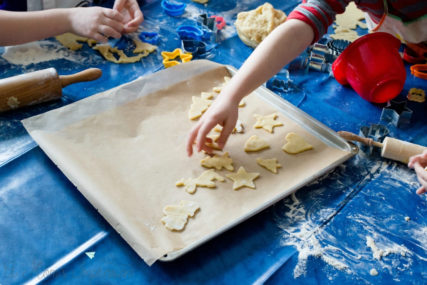 child's hands cutting Christmas cookies