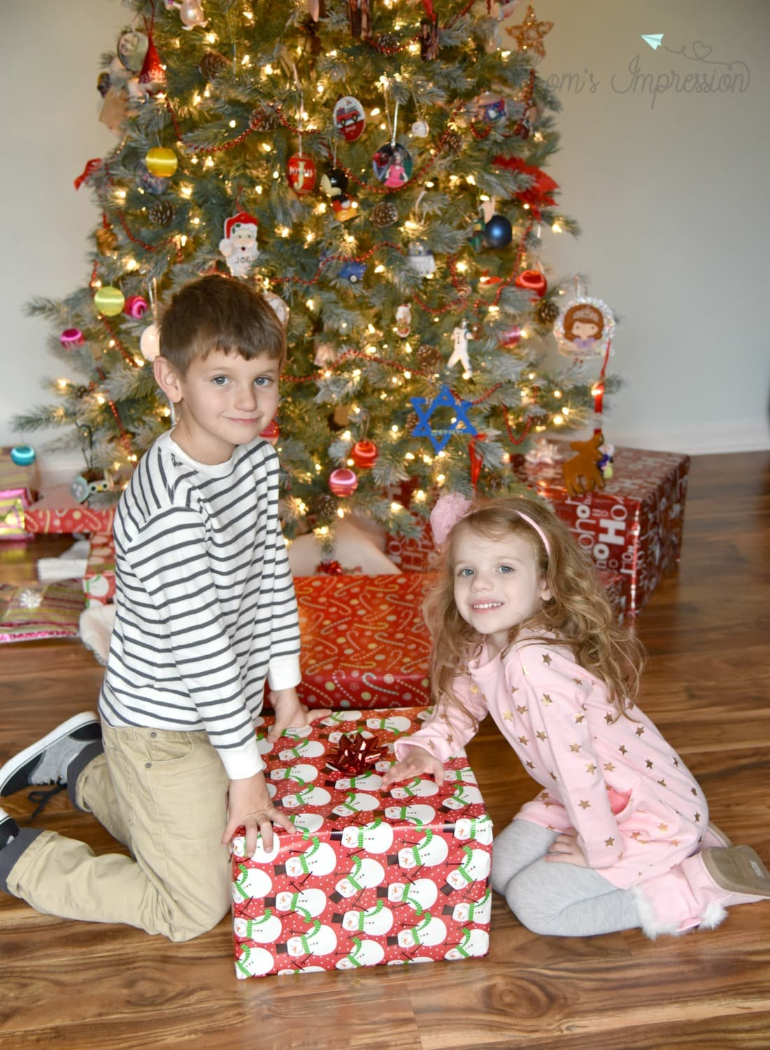 two kids in front of a christmas Tree