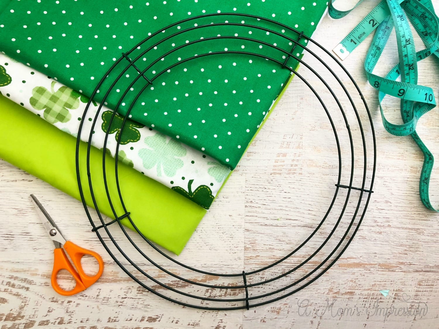 st patricks day wreath supplies include fabric, scissors and a frame.