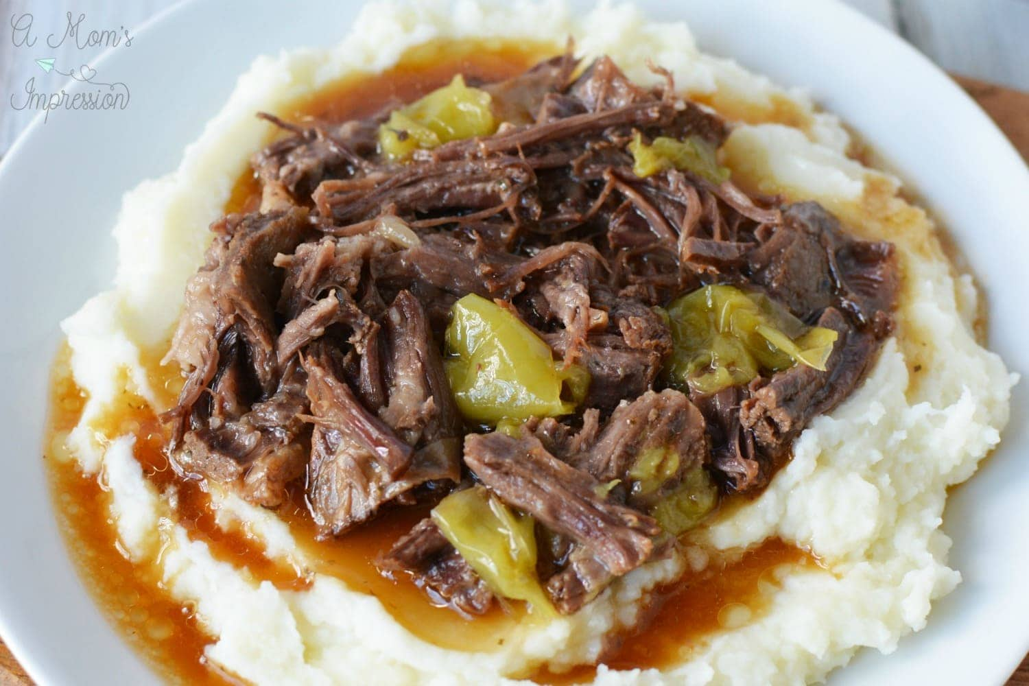 instant pot beef roast with pepperoncinis and mashed potatoes on a white plate.