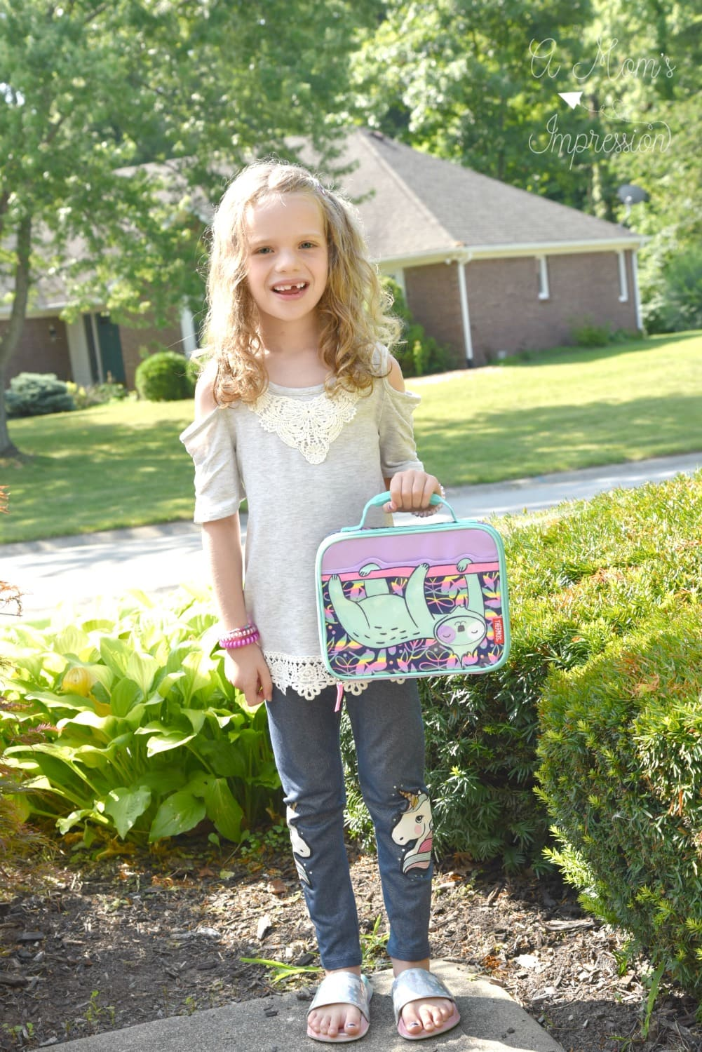 Child holding a lunchbox wearing new clothes