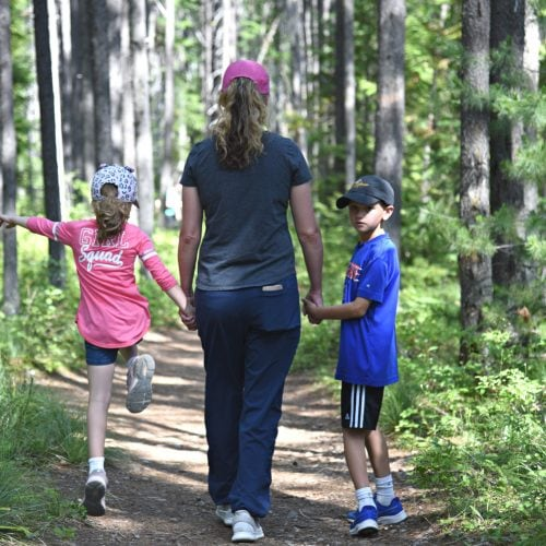 a mom, son and daughter hiking in the woods