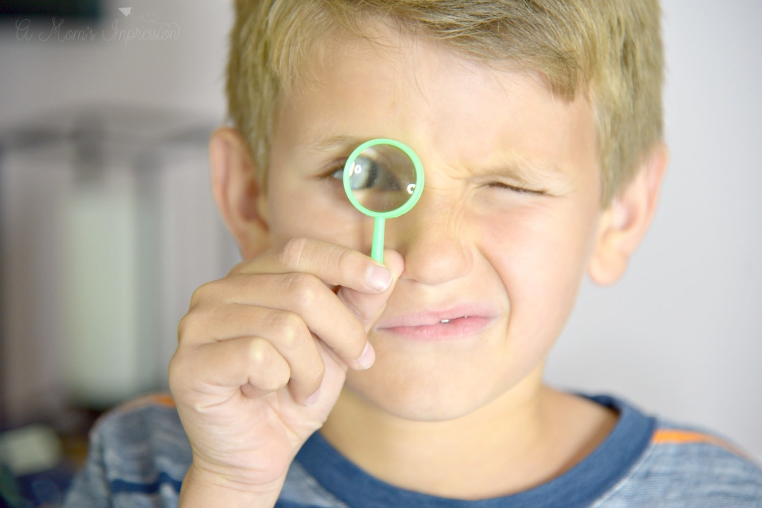 a boy with a tiny magnifying glass