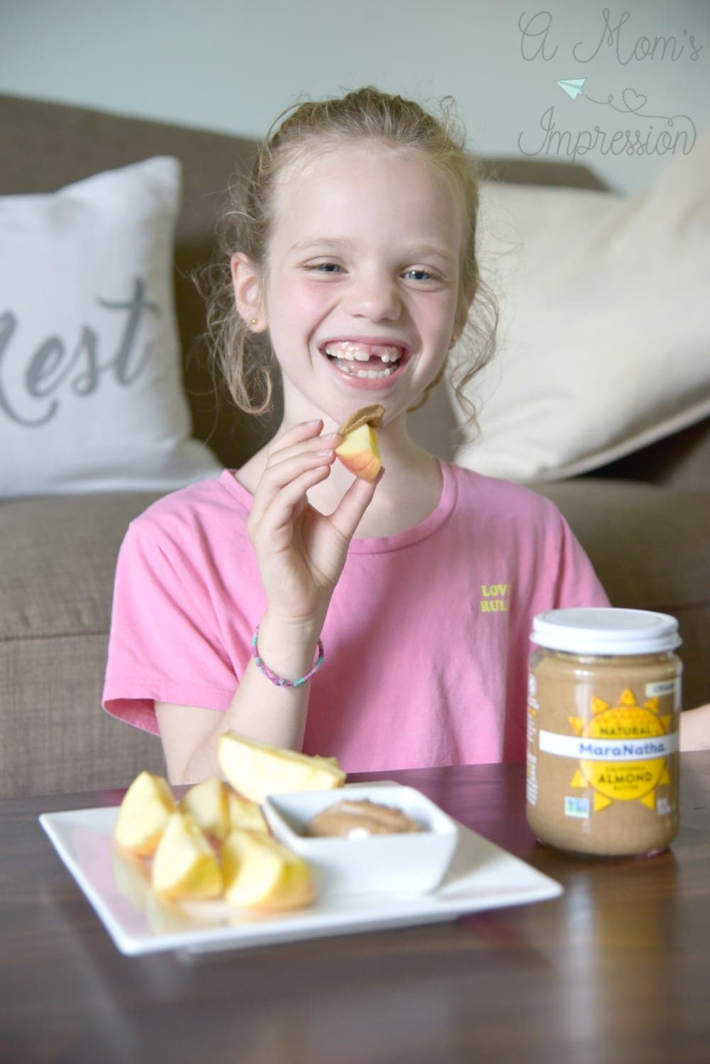 girl eatting apples and an almond butter snacks