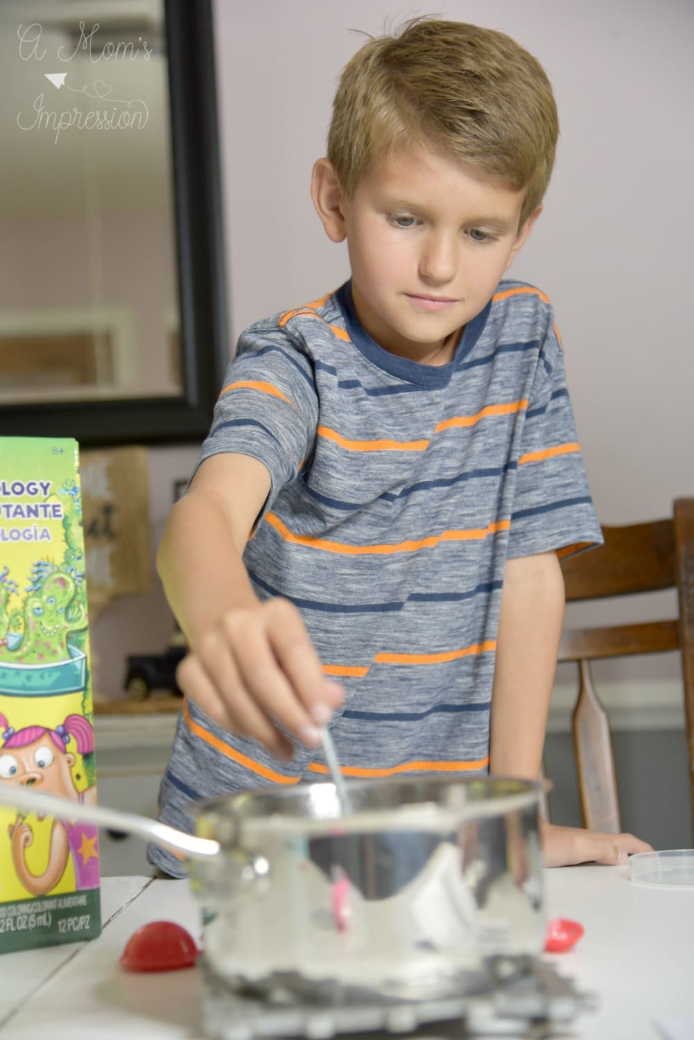 boy playing with stiring science experiment in a saucepan