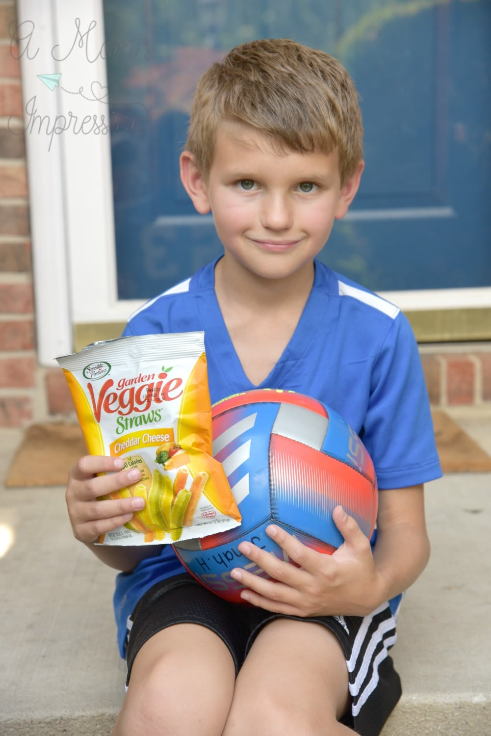 boy eating veggie straws on front porch