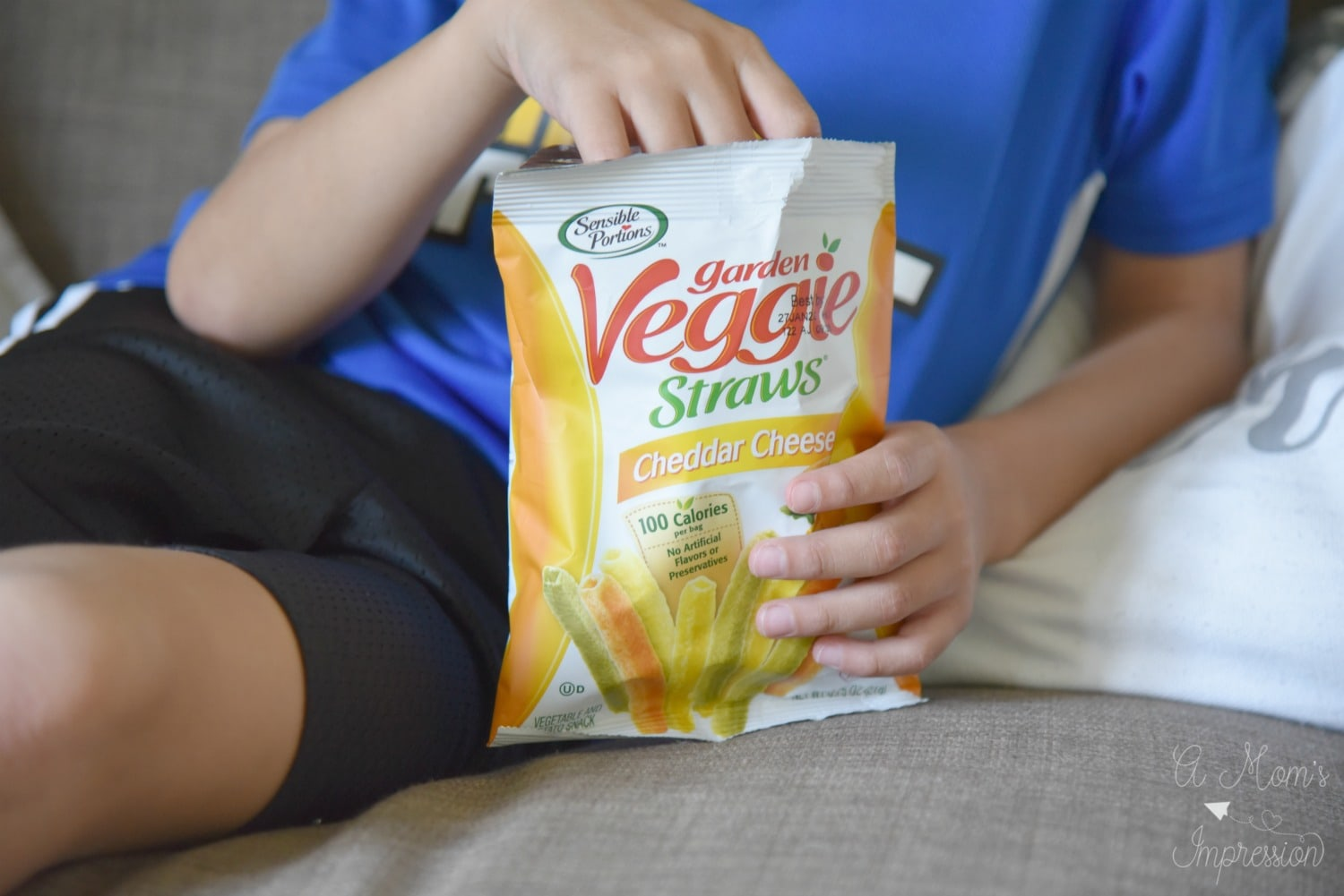 a boy grabbing veggies straws out of a bag
