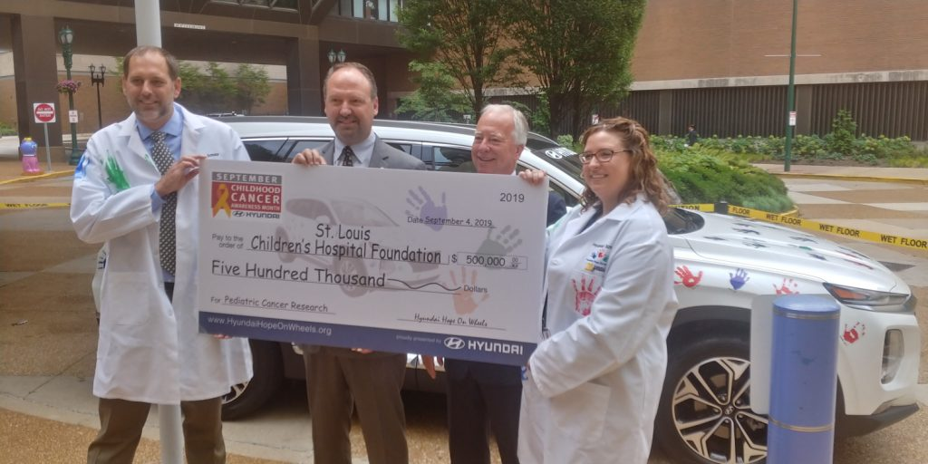 A large check held by four peole for Childhood cancer funding