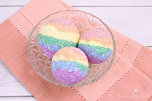 Three DIY rainbow bath bombs sitting in a bowl on a table