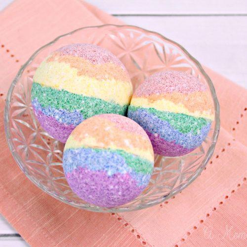 Three DIY rainbow bath bombs sitting in a bowl on a table
