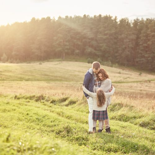 a mom, dad, and female child embracing in a field
