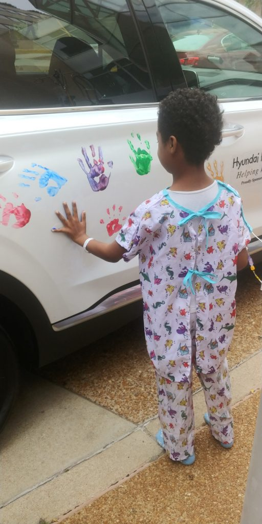 Hyundai Hope on Wheels child putting his handprint on a white car