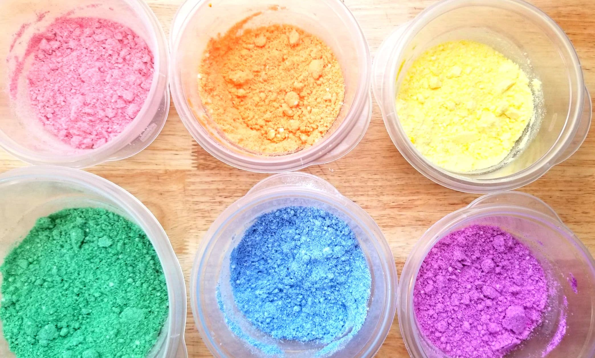 small bowls of differently colored bath bomb ingredients