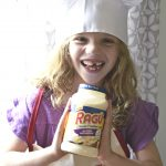 child wearing ragu apron and a chefs hat with a bottle of ragu sauce in her hands