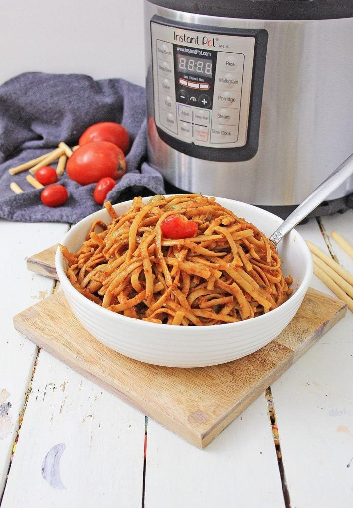 a bowl of instant-pot-pasta sitting on a cutting board in front of a pressure cooker