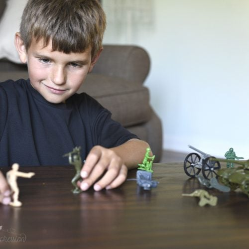 a young boy sitting at a table playing with army men and tanks