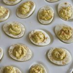 Deviled eggs sitting in an egg serving platter