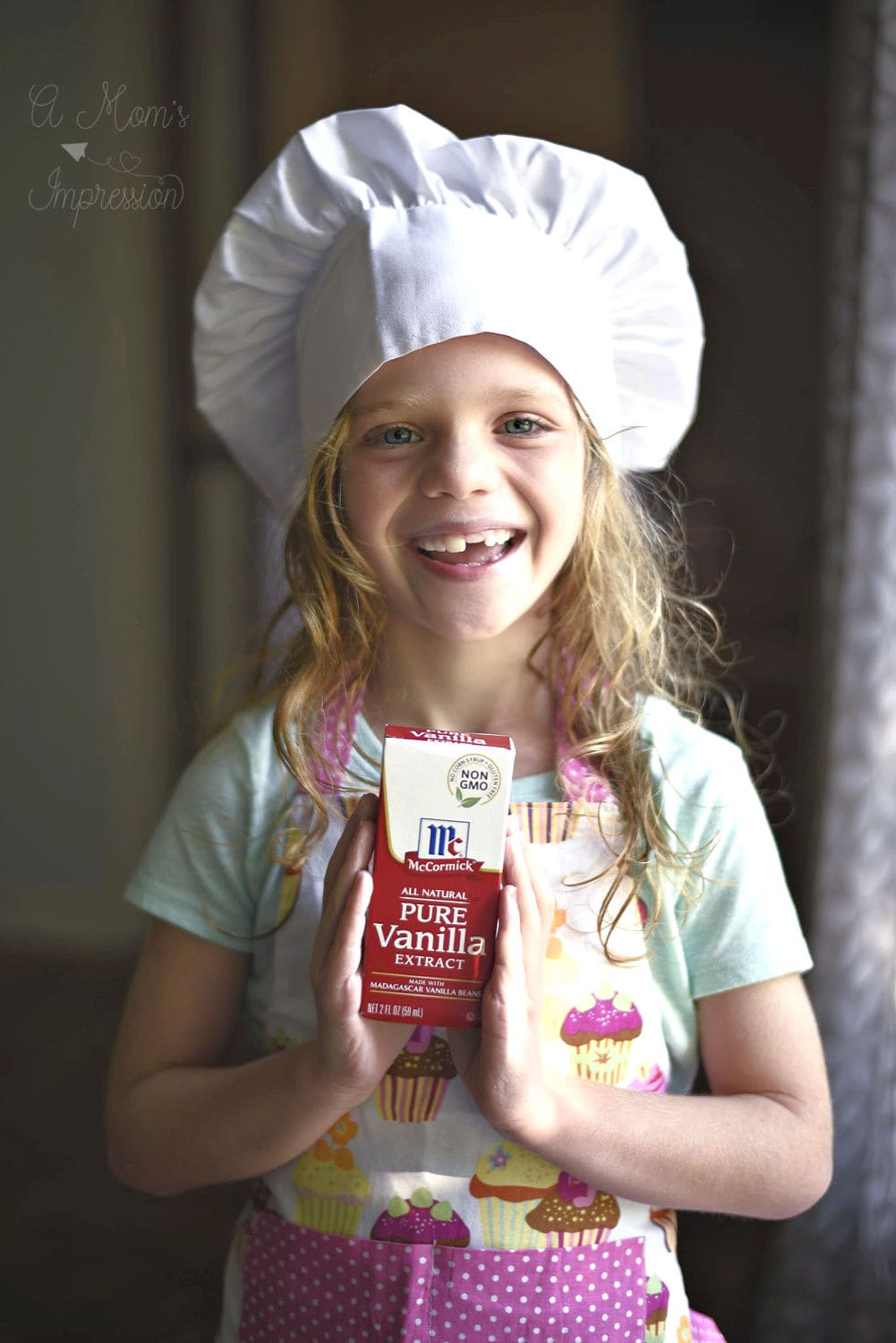 a girl in a chefs hat holding mccormicks spices