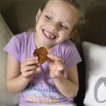 a little girl eating chicken fingers