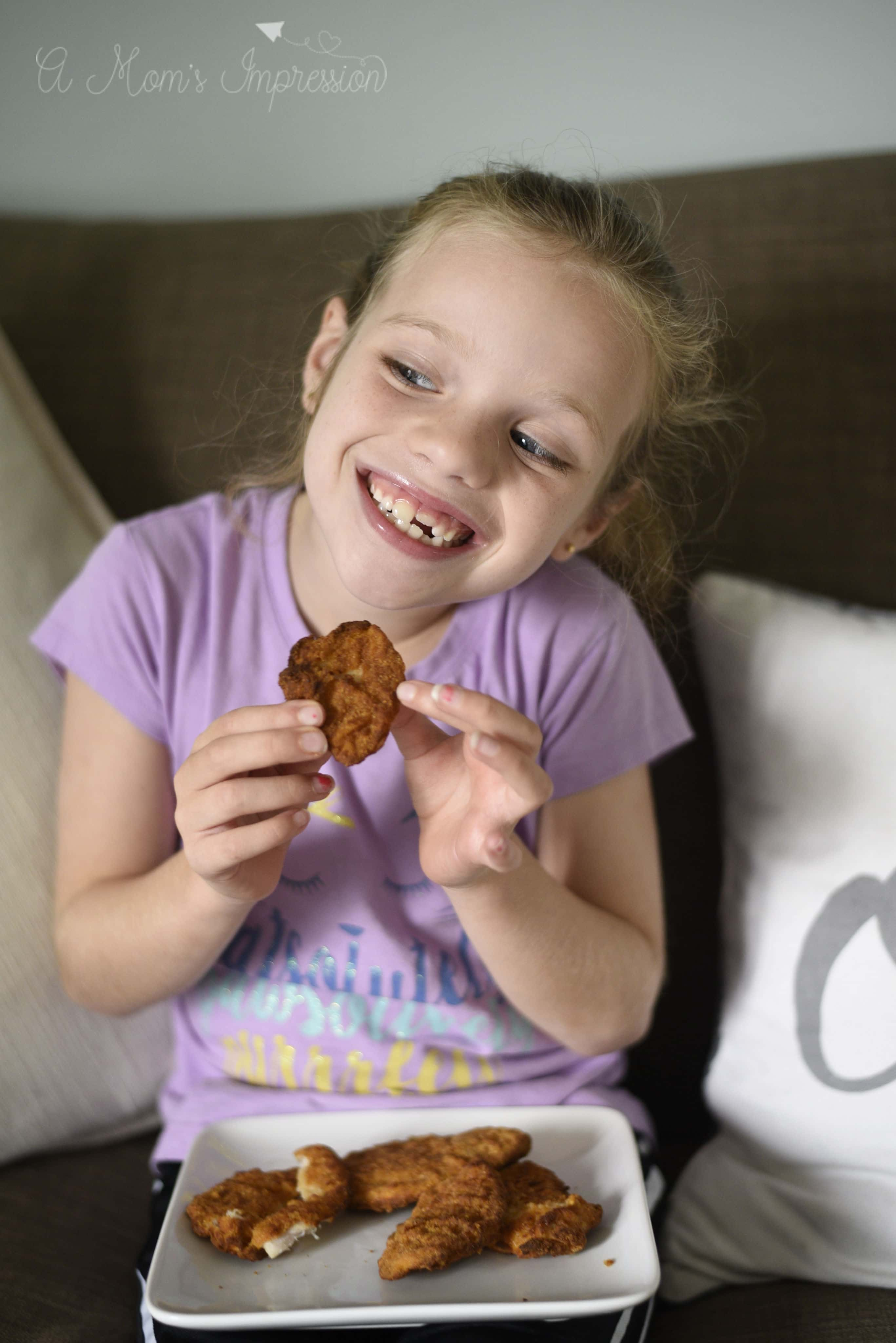 a little girl eating chicken fingers