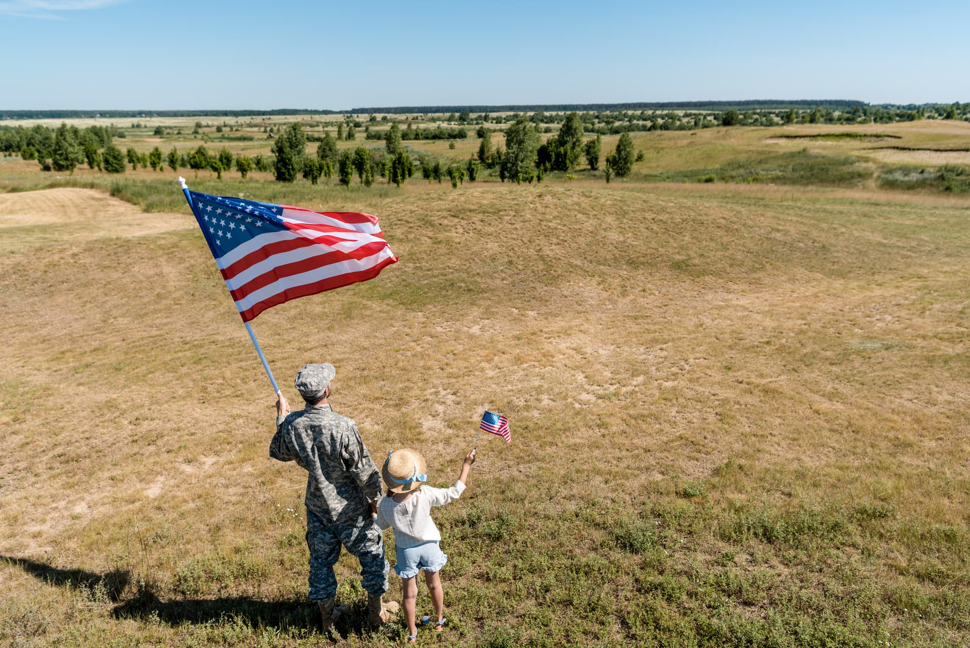 a child and her military dad carrying a flag