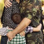 a child and his military parents embracing