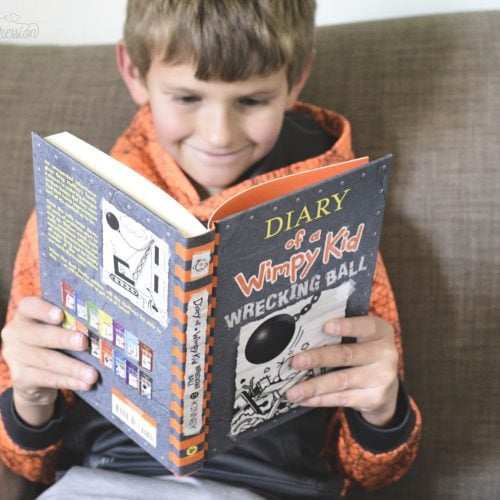 a boy reading Diary of a Wimpy kid