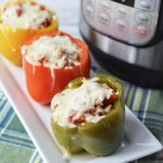 Instant Pot Sausage stuffed peppers on a white plate with a pressure cooker in the background