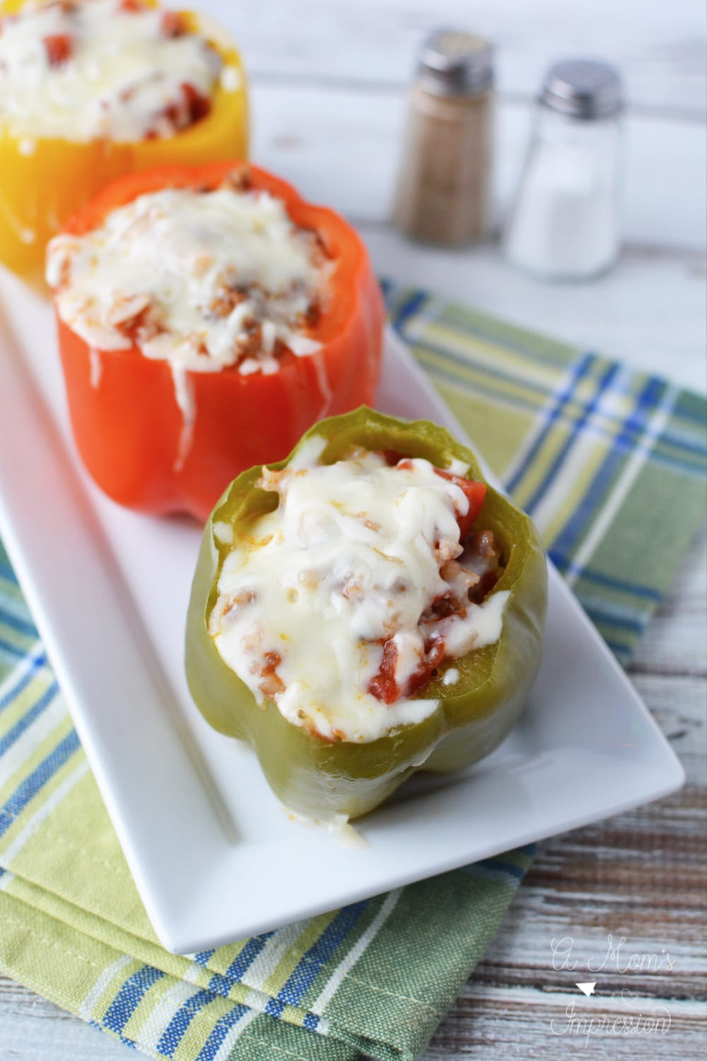 three peppers on a white plate with melted cheese on top of them
