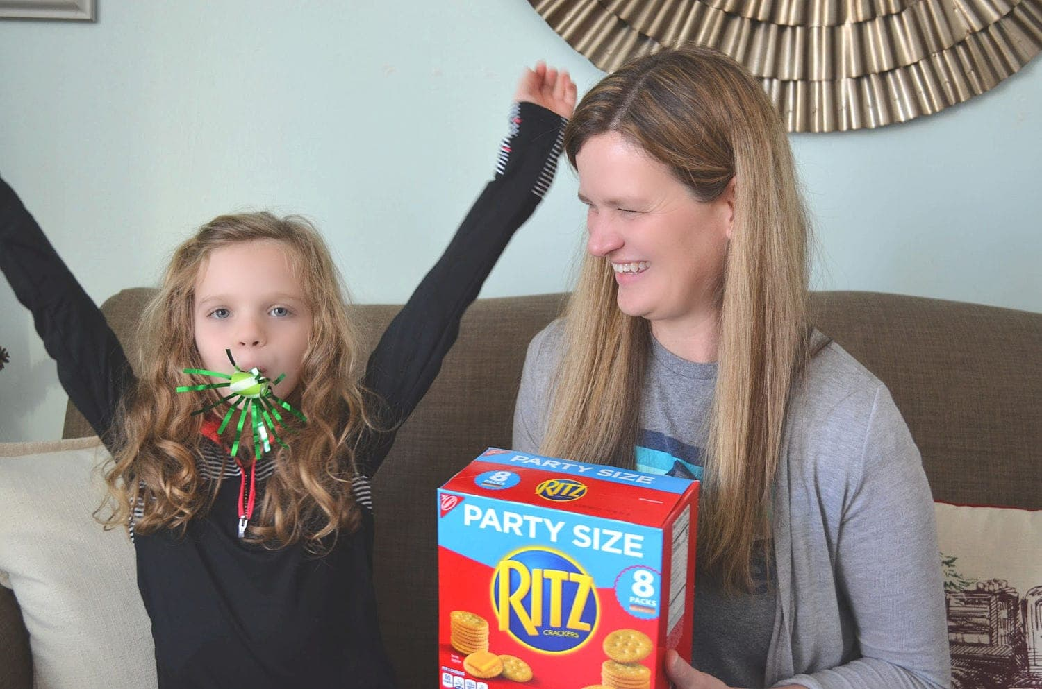 A girl with a party whistle in her mouth with her mom on a sofa with a box of ritz crackers