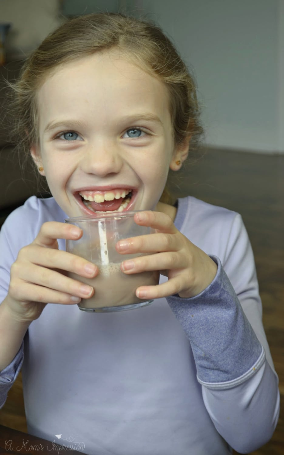 a little girl smiling while drinking chocolate milk from a glass