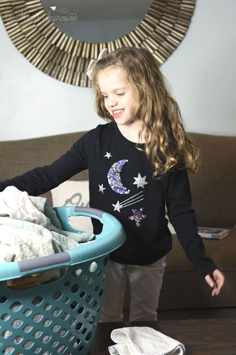 A child Folding Clothes out of a laundry basket