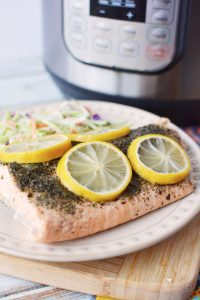 A plate with some salmon and lemon slices sitting in front of an Instant Pot pressure cooker