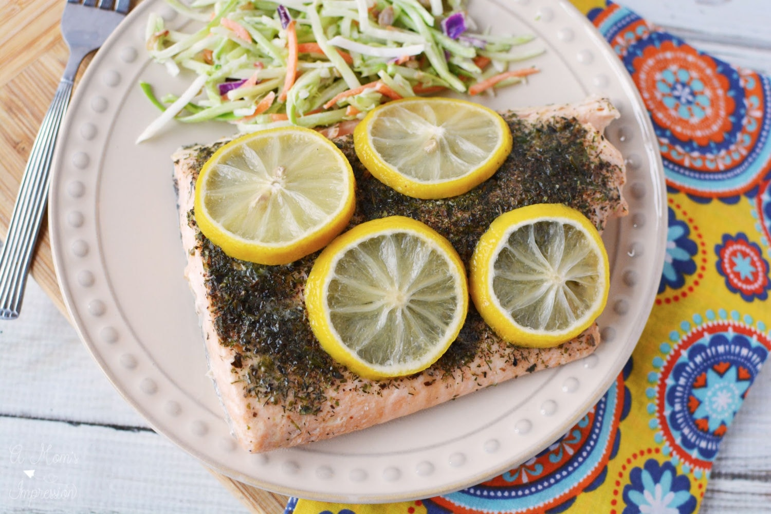 A plate of Pressure Cooker Salmon with Lemon sitting on a colorful napkin on a wood table