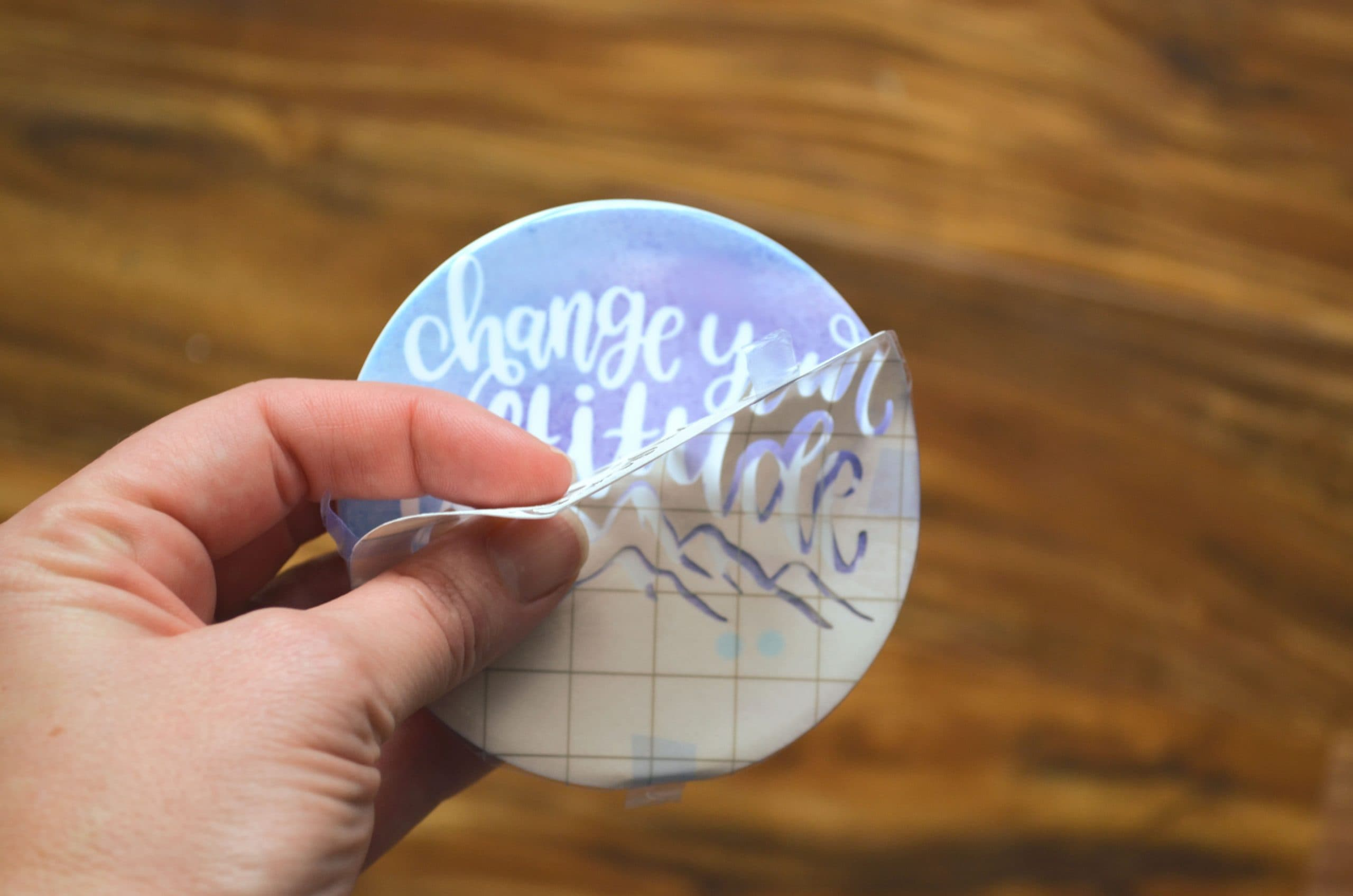 peeling away a stencil from a cricut diy coasters