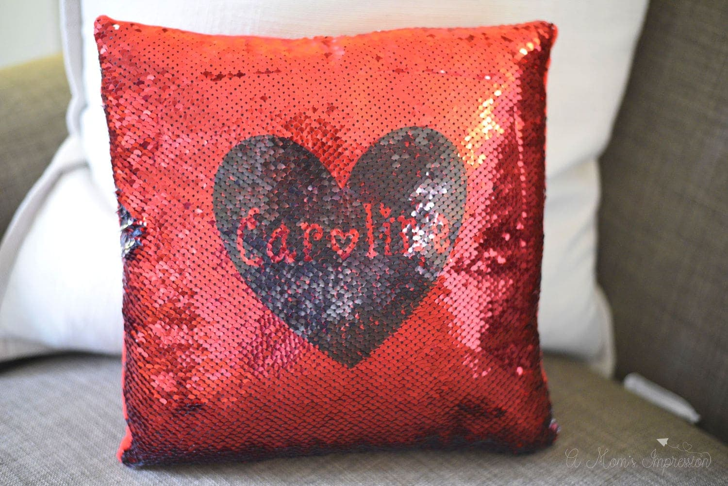 Red customized sequin pillow sitting on a sofa