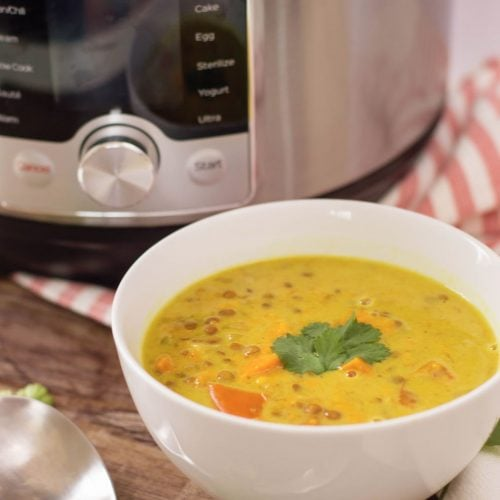 a bowl of sweet potato curry sitting in front of a Pressure cooker