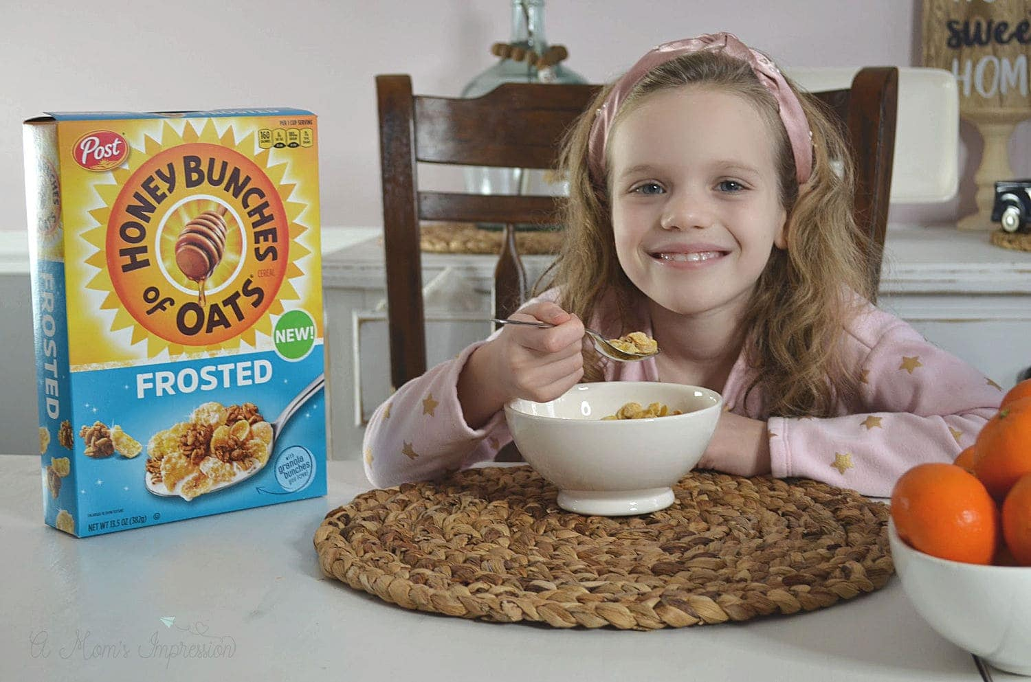 a girl smiling a she is eating breakfast cereal