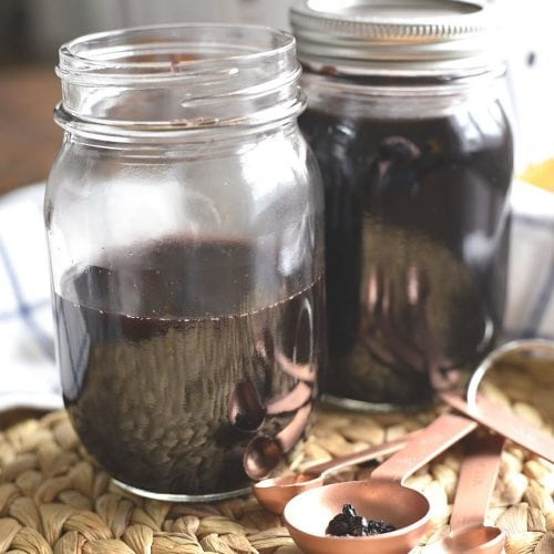 Two jars of homemade elderberry syrup in front of an Instant pot
