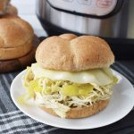 a Instant Pot Mississippi Chicken sandwich sitting in front of a pressure cooker