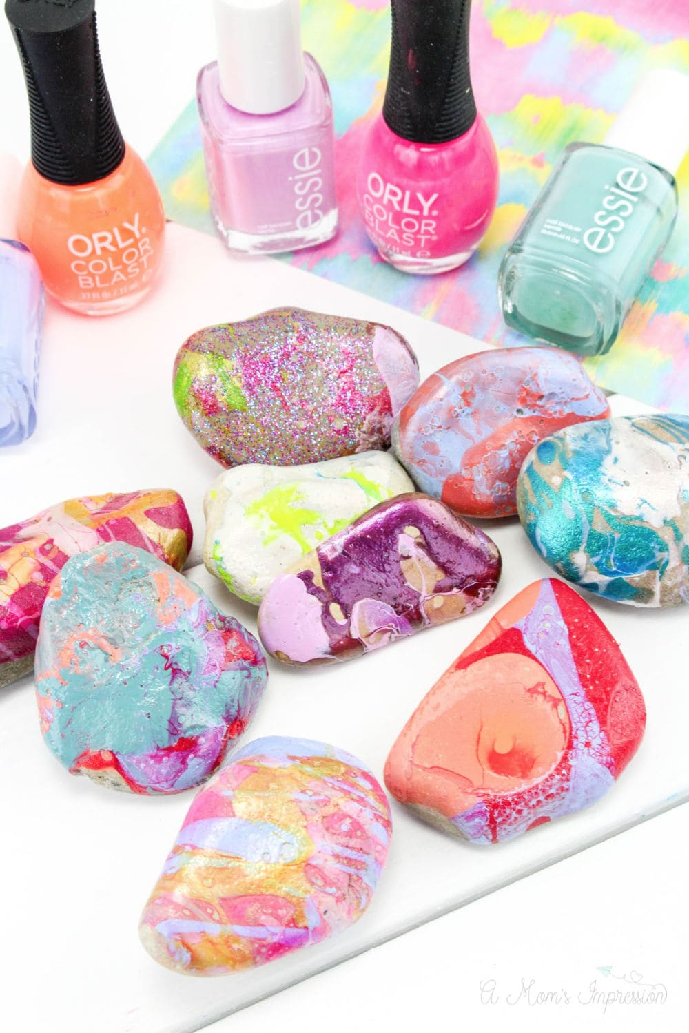 nail polish painted rocks with nail polish bottles sitting behind them