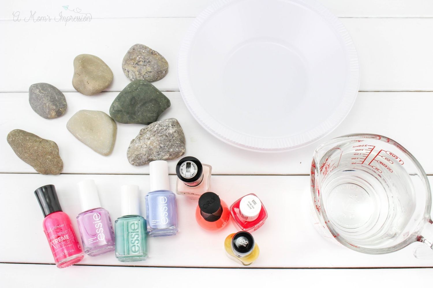 some rocks, nail polish, water and a bowl sitting on a white surface