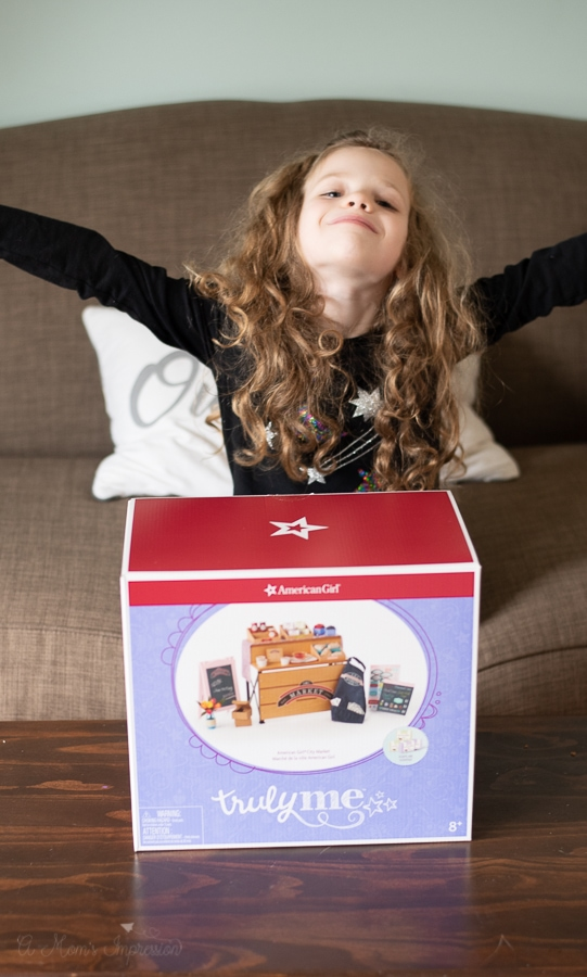 Girl spreading her arms in excitement with a box that includes am american girl playset in it.