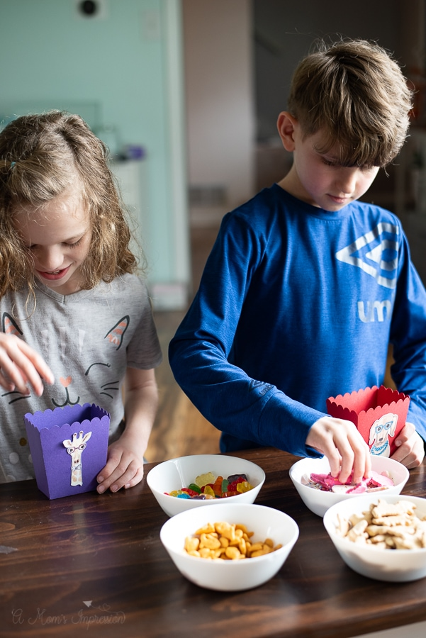 two children filling up treat boxes with animal themed food